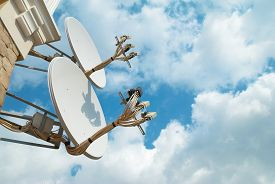 stock photo of antenna  - Satellite antenna on the wall with blue sky - JPG