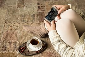 pic of crossed legs  - Female cross legged on the carpet with her smartphone - JPG