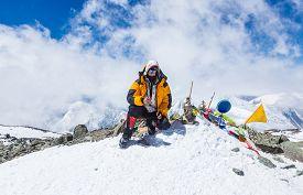 stock photo of lenin  - Mountain climber at the top of Lenin Peak Pamir Mountains Kyrgyzstan - JPG