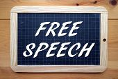 picture of freedom speech  - The phrase Free Speech in white text on a slate blackboard placed flat on a wooden surface - JPG