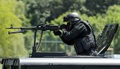 stock photo of smuggling  - special force unit assault team attacks with heavy machine gun - JPG
