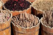 picture of stall  - cinnamon sticks and dried hibiscus petals in wooden container on street stall in tropical country - JPG