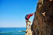picture of mountain-climber  - climber with backpack climbing on top of mountain - JPG