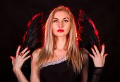 foto of hells angels  - Beautiful young woman with black angel wings over dark red background - JPG