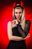foto of demon  - Beautiful young woman with red demon horns over red and black background - JPG