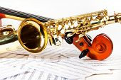 Постер, плакат: Cello tuning pegs and shiny golden alto saxophone