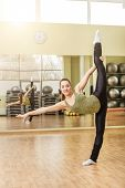 stock photo of do splits  - Young slim woman doing standing split at gymnastics training in fitness class - JPG