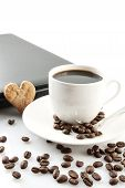 stock photo of coffee crop  - Cropped cup of black coffee with laptop saucer scattered coffee beans at breakfast on white background - JPG