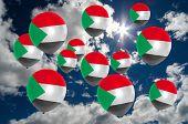 stock photo of sudan  - many ballons in colors of sudan flag flying on sky - JPG