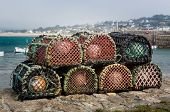 stock photo of trap  - Rope and wooden frame lobster pot or trap stacked on stone wall of harbor on south coast of England - JPG