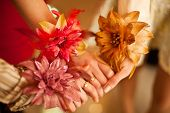 stock photo of matron  - Three girls shaken hands with flowers on wrists - JPG