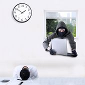 stock photo of felon  - Male thief wearing mask and stealing a laptop in the office through a window when the employee is sleeping - JPG