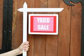 stock photo of yard sale  - Wooden Yard Sale sign in female hand on wooden fence background - JPG