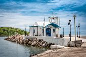 foto of chapels  - Small chapel with white roofs on cliff over sea and small bay under a dramatic sky on a Greek island - JPG