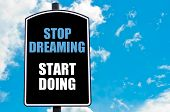picture of start over  - STOP DREAMING START DOING motivational quote written on road sign isolated over clear blue sky background with available copy space - JPG