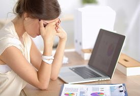 stock photo of disappointed  - Portrait of tired young business woman with laptop computer  - JPG