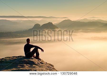 Hiker In Black On The Rocky Peak. Wonderful Daybreak In Mountains, Heavy Orange Mist In Valley. Man