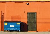 Blue Dumpster & Orange Wall