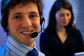 Male and female customer service representative working in office, smiling.