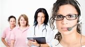 Young female cinic receptionist wearing glasses and headset, medical team in background. Isolated on