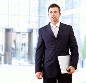 Determined successful businessman standing and holding laptop computer in hand, outdoor in front of