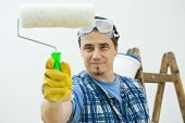 Worker painting with roller, isolated on white background.