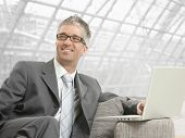 Businessman wearing grey suit and glasses, sitting on couch with laptop computer in office lobby, sm