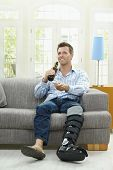 Man watching TV at home, sitting on couch, holding remote control in hand, drinking beer.