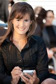 Happy young businesswoman sitting in chair, using smart phone.
