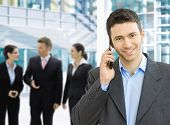foto of motivation talk  - Portrait of happy businessman talking on mobile in office lounge - JPG