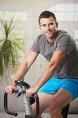 Man training on exercise bike at home, listening music.