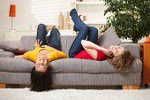 Meninas adolescentes felizes descansando no sofá em casa, sorrindo.