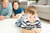 Happy family lying on floor in living room. Selective focus on little boy.