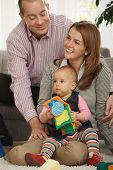 stock photo of nuclear family  - Portrait of happy family of three sitting together in living room - JPG