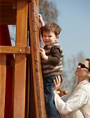 Happy mother helping little boy to climb wooden jungle gym on playground, sunlit outdoor.