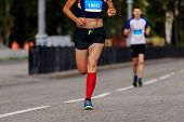 Постер, плакат: Female Athlete Runner Ahead Man Runner In City Marathon