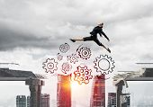 Business Woman Jumping Over Gap With Gear Mechanism In Concrete Bridge As Symbol Of Overcoming Chall poster