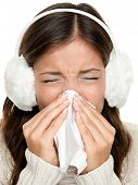 Flu or cold - sneezing woman sick blowing nose. Young woman being cold wearing earmuffs and sweater.