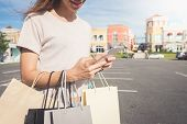 Close Up Of A Young Woman Hold A Shopping Bags In Her Hand And Chatting On Her Phone After Shopping. poster