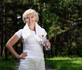 stock photo of elderly woman  - An elderly woman after exercising in the forest holding a bottle of water - JPG