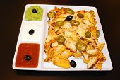 Mexican Nachos With Chicken On Black Bacground. Nachos With Tortilla Chips, Cheese, Salsa, Guacamole poster