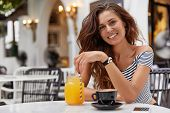 Positive Adorable Young Woman With Dark Wavy Hair, Recreats Alone At Cafeteria With Various Beverage poster