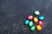 Heap Of Easter Eggs Decorated Confetti On Black Table Top View. Copy Space For Text. poster