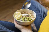 Eating Healthy Breakfast Bowl. Yogurt, Buckwheat, Seeds, Fresh Fruits In White Bowl In Woman S Hand poster