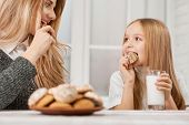 Photo Of Mother And Daughter Eating Cookies And Smile. poster
