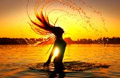 Beauty Model Girl Splashing Water with her Hair. Model girl silhouette over sunset sky. Swimming and poster