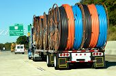 foto of 18 wheeler  - eighteen wheeler hauls large load of spindles of plastic hose - JPG