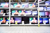 Plasma TVs with big diagonal stand on shelves in large shop; wide range