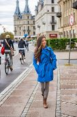 Asian tourist woman walking in Copenhagen city street next to bike path, modern commute. Urban livin poster