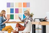 Fashionable Magazine Editors Working With Smartphones At Workplace With Color Palette On Wall poster
